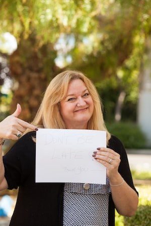 Pam Didier holding a sign so people aren't late to Addiction Recovery